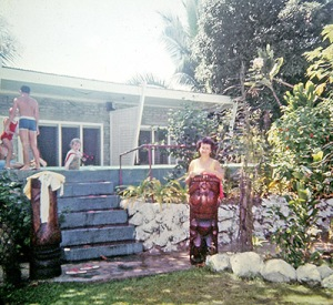 Jean stands behind a tikki in front of the pool at Aggie Greys.