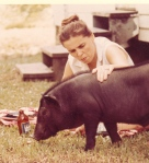 Neighbor Gloria M. with Unka the pig, who appears to be very interested in the bottle of beer in front of him.
